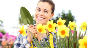 Springtime, smiling woman  in garden takes care of flowers Royalty Free Stock Images