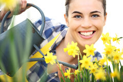 Springtime, smiling woman in garden with watering can Stock Photos