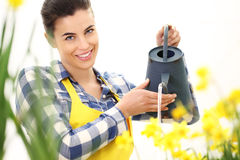 Springtime, smiling woman  in garden with watering can Stock Photo