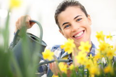 Springtime, smiling woman in garden with watering can Royalty Free Stock Photography