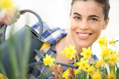 Springtime, smiling woman in garden with watering can, watering Stock Images