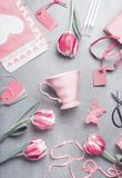 Springtime still life flat lay with pastel pink tulips, hearts, mug , gifts, tags and scissors, top view. Layout or greeting card Stock Photography