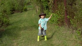 Springtime or summertime for kids on the ranch. Eco Resort Activities. Boy in a gumboots planting on the spring field stock video