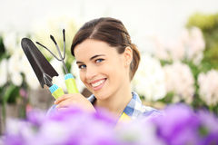 Springtime woman smiling in garden with tools in hands. Springtime happy woman smiling in garden with tools in hands Royalty Free Stock Image