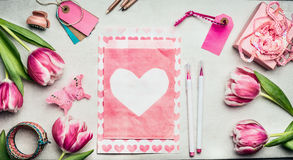 Springtime womens workspace with pink tulips flowers, paper envelope with heart, brush markers, tags and gift box, top view, copy Stock Images
