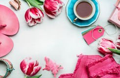 Springtime womens workspace with tulips flowers, pink clothes and shoes, tags and coffee cup, top view royalty free stock images