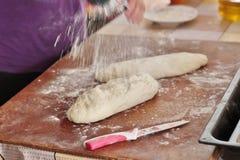 Sprinkilings-Mehl auf Brotteig Stockfoto