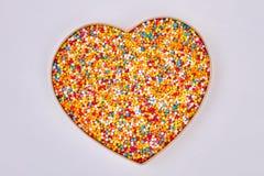 Sprinkle dots, heart shaped box. Sugar sprinkles on white background. Saint valentine present stock photo