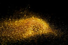 Sprinkle glitter gold dust. On a black background with copy space Royalty Free Stock Photos
