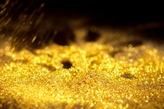 Sprinkle glitter gold dust on a black background Royalty Free Stock Image