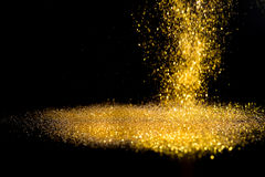 Sprinkle gold dust on a black background. With copy space Royalty Free Stock Images