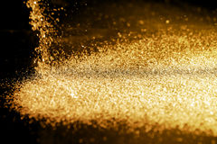 Sprinkle gold dust. On a black background with copy space Stock Image