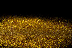 Sprinkle gold dust on a black background. With copy space Royalty Free Stock Image