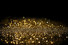 Sprinkle gold dust on a black background. With copy space Stock Photo
