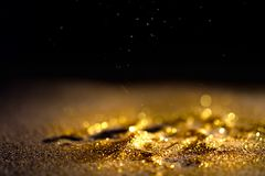 Sprinkle gold dust glitter. Sprinkle gold dust on a black background with copy space Stock Image