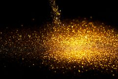 Sprinkle gold glitter dust on a black background. With copy space Stock Images