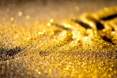 Sprinkle gold shiny dust. On a black background with copy space Royalty Free Stock Photo