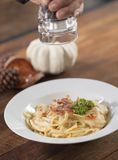 Sprinkle spices on Spaghetti Carbonara. On white dish Stock Image