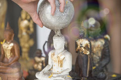 Sprinkle water onto a Buddha image, Season background Royalty Free Stock Photography