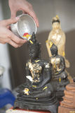 Sprinkle water onto a Buddha image, Season background Stock Photos