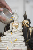 Sprinkle water onto a Buddha image, Season background Royalty Free Stock Photo