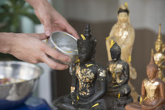 Sprinkle water onto a Buddha image, Season background Royalty Free Stock Images