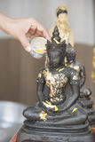 Sprinkle water onto a Buddha image, Season background Royalty Free Stock Photos