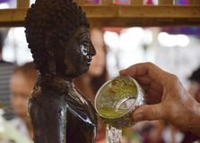 Sprinkle water onto a Buddha Stock Images