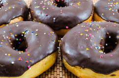 Sprinkled Donuts on Placemat. Chocolate iced dunuts with sprinkles on placemat Stock Photos