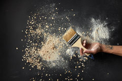 Sprinkled flour over background. Background after cooking fresh and delicious bread of different kinds. Woman`s hand with tatto holding brush for cooking over royalty free stock photos
