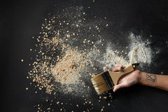 Sprinkled flour over background. Food industry concept. Background after cooking fresh and delicious bread of different kinds. Woman`s hand with tatto holding royalty free stock photography