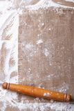 Sprinkled flour and rolling pin on a wooden board and burlap Stock Images