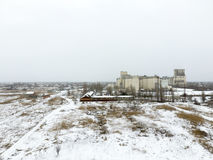 Sprinkled with snow grain elevator. Winter view of the old Soviet elevator. Winter view from the bird's eye view of the village.  Stock Photos