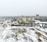 Sprinkled with snow grain elevator. Winter view of the old Soviet elevator. Winter view from the bird's eye view of the village.. The streets are covered with Royalty Free Stock Photo
