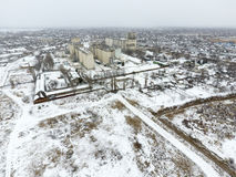 Sprinkled with snow grain elevator. Winter view of the old Soviet elevator. Winter view from the bird's eye view of the village.. The streets are covered with Stock Images