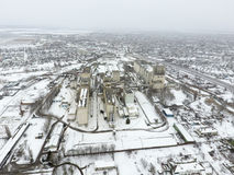 Sprinkled with snow grain elevator. Winter view of the old Soviet elevator. Winter view from the bird's eye view of the village.. The streets are covered with Royalty Free Stock Image