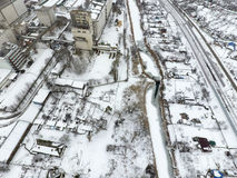 Sprinkled with snow grain elevator. Winter view of the old Soviet elevator. Winter view from the bird's eye view of the village.. The streets are covered with Stock Photo