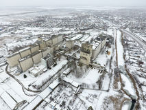 Sprinkled with snow grain elevator. Winter view of the old Soviet elevator. Winter view from the bird's eye view of the village.. The streets are covered with Stock Photography