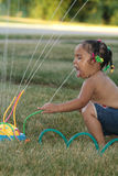 The sprinkler. A toddler getting a drink from her sprinkler Stock Photo
