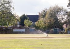 Sprinkler in action water spray on cricket green field Royalty Free Stock Image