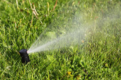 Sprinkler aiding water distribution to lawn Stock Photo