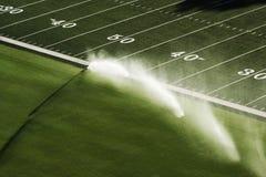 Sprinkler on football field Stock Images