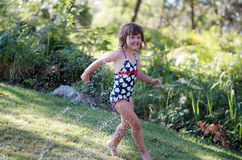 Sprinkler fun. Little girl running in garden having fun with water sprinkler stock photo