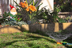 Sprinkler and gnome in garden. Sprinkler and gnome with flowers in garden Stock Image