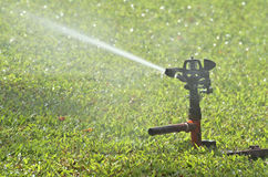 Sprinkler on green grass. Sprinkler watering the green grass Stock Photography