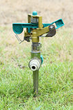 Sprinkler on the green grass Stock Images