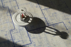 Sprinkler Head and Blueprints. Sprinkler head casting a shadow on blueprints Royalty Free Stock Photography