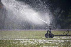 Sprinkler head watering the grass in sport field. Stock Images