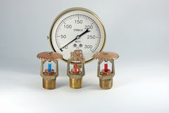 Sprinkler heads and gauge. Glass filled sprinkler heads and a sprinkler gauge over white Royalty Free Stock Photos