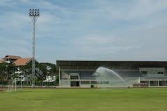 Sprinkler spray water to grass field in football stadium. Stock Photo